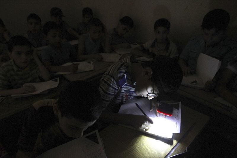Học sinh đeo đèn trên đầu do thiếu điện khi tham gia kỳ thi cuối năm ở một trường thuộc al-Sha'ar , Aleppo, Syria ngày 5/6/2013. Ảnh: Reuters