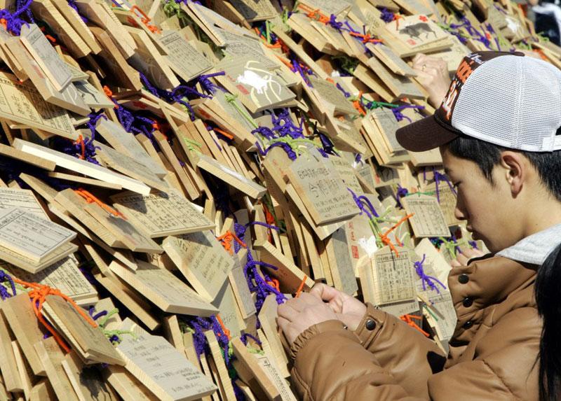Một học sinh đang buộc mảnh gỗ may mắn trong sân đền Yushima Tenjin, Tokyo, Nhật Bản để cầu may ngày 19/1/2008. Ảnh: AP