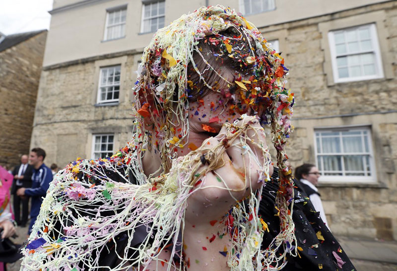 """Một sinh viên của University College Oxford bị """"đổ rác"""" lên đầu sau khi hoàn thành kỳ thi vào ngày 7/6/2013. Đổ rác lên đầu là một truyền thống ở ĐH Oxford sau khi kết thúc các kỳ thi. Ảnh: Reuters"""