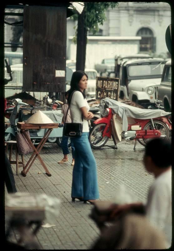 Quần ống loe là dấu ấn đặc trưng thời trang thập niên 70 cũng được các quý cô Sài Gòn đón nhận nhanh chóng. Phụ nữ Sài Gòn tại công trường Lam Sơn, Sài Gòn năm 1969, bên phải là cư xá Eden.