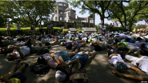 Trẻ em nằm tại Vòm Bom Nguyên tử để tưởng nhớ hàng ngàn người thiệt mạng.
