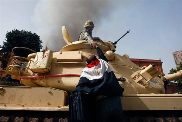 Một người đàn ông Ai Cập đang bắt tay một binh sĩ quân đội để tỏ lòng biết ơn sau khi họ khẳng định sẽ không nổ súng vào những người dân vô tội tại thủ đô Cairo vào năm 2011.