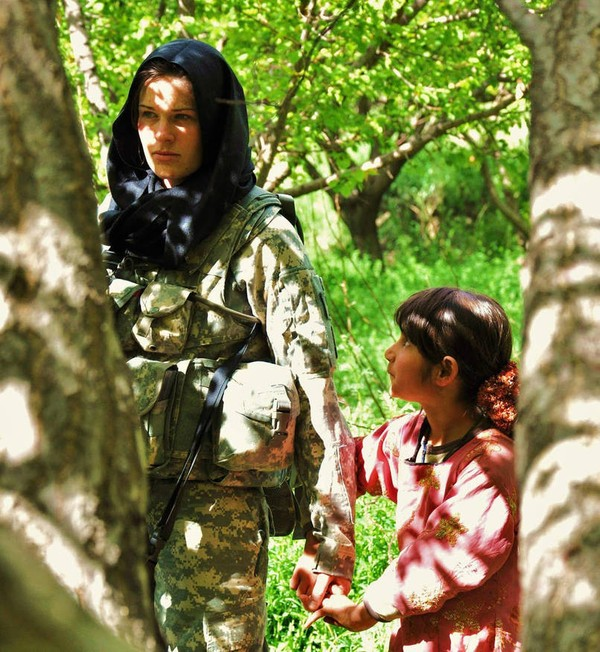 Nữ binh lính người Mỹ đang nắm tay một bé gái người Afghanistan trước ánh mắt ngạc nhiên của cô bé.
