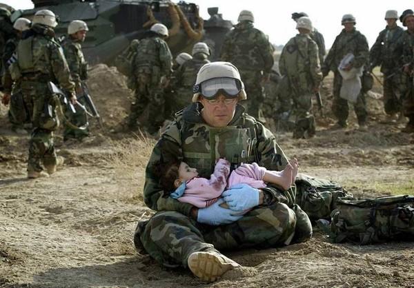 Vẻ mặt mệt mỏi xen lẫn nhẹ nhõm hiện trên khuân mặt của một người lính hải quân Mỹ khi đã cứu được một cô bé bị lạc mất gia đình trong chiến tranh tại Iraq vào năm 2003.