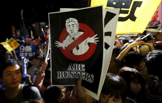 A protester holding a placard depicting Japan's Prime Minister Shinzo Abe takes part in a rally against Abe's security bill and his administration in front of the parliament in Tokyo, Japan, September 16, 2015. REUTERS/Yuya Shino