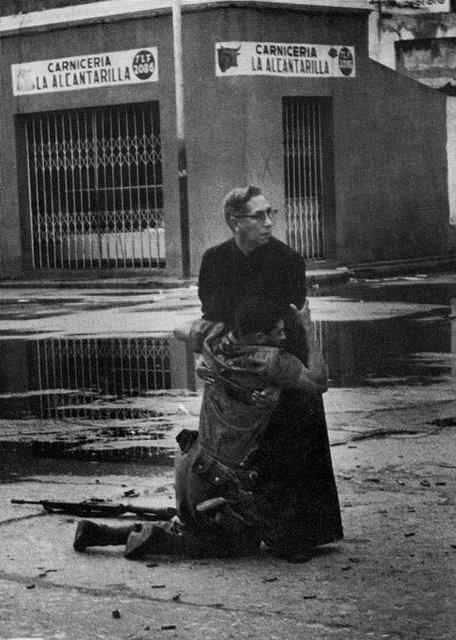 Vị linh mục đang an ủi một người lính bị thương gục ngã trên tay ông sau khi phải chứng kiến quá nhiều cái chết của các đồng đội.