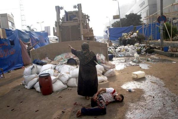 Người phụ nữ Ai Cập đang cố gắng chặn một xe ủi đất quân sự để ngăn không cho chiếc xe này chèn qua một thanh niên đang bị thương nặng trong cuộc đụng độ gần ngôi đền thờ Hồi giáo Rabaa al- Adawiya ở miền Đông Cairo.