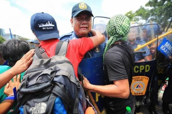"""Joselito Sevilla, một cảnh sát người Philippines có đã bật khóc nức nở trong khi đang cố gắng làm nhiệm vụ ngăn cản dòng người biểu tình vào ngày 22/7/2013 tại thủ đô Manila. Cuộc biểu tình diễn ra trong bối cảnh có quá nhiều người phản đối chính sách giảm nghèo đói của Tổng thống Benigno Aquino. Khi bị một người biểu tình mắng nhiếc, người cảnh sát đã bật khóc nức nở: """"Tôi là một cảnh sát. Tôi chỉ đang làm công việc của mình"""". Bức ảnh này đã khiến cộng đồng mạng chấn động."""
