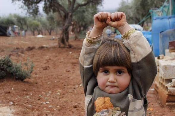 Bé Adi Hudea, 4 tuổi, người Syria mím chặt môi và giơ tay đầu hàng vì tưởng máy ảnh là súng khi phóng viên chụp em tại trại tị nạn Atmen ở biên giới Syria - Thổ Nhĩ Kỹ. Ngay sau khi xuất hiện trên Internet ngày 31/3, bức ảnh thu hút sự chú ý của toàn thế giới với hơn 11.000 lượt chia sẻ trên Twitter và nhiều trang mạng xã hội khác. Bức ảnh cho thấy hậu quả khủng khiếp của cuộc nội chiến ở Syria và số phận đáng thương của dân thường vô tội, khiến những đứa trẻ mất tính hồn nhiên. Ảnh: Daily Mail