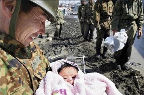 4 ngày sau trận động đất và sóng thần ở Nhật Bản tháng 3/2011, những người lính cứu hộ tìm thấy một em bé 4 tháng tuổi còn sống sót trong đống đổ nát. Bức ảnh tạo niềm tin về những kỳ tích trong thảm họa. Ảnh: Buzzfeed