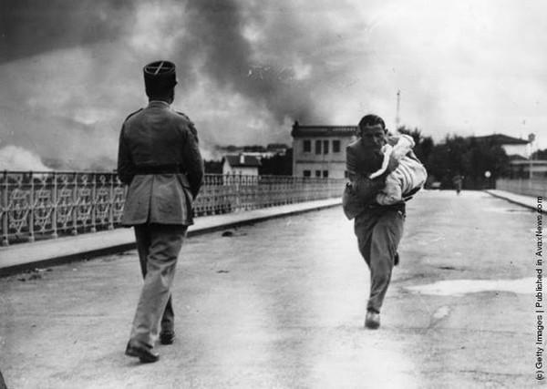 Nhà báo Raymond Walker đang bế trên tay một em bé mà ông vừa cứu được trong cuộc nội chiến Tây Ban Nha vào năm 1936. Ông vội vã băng qua một chiếc cầu dẫn đến Pháp giữa làn khói đạn mịt mù.