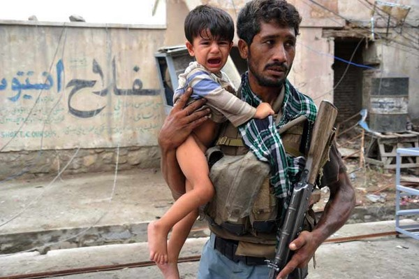 Người lính Afghanistan giải cứu một em bé đang khóc vì sợ hãi ra khỏi hiện trường một vụ nổ trong cuộc chiến tranh Afghanistan (2001-2014).