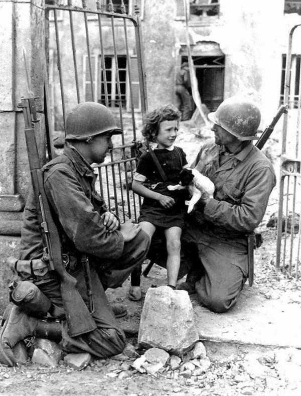 Hai người lính Mỹ đang cố gắng đem niềm vui đến cho bé gái trong Chiến tranh Thế giới thứ hai.