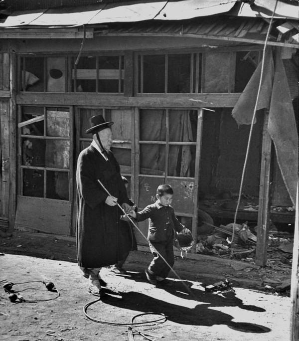 Cậu bé giúp đỡ cụ già bị mù băng qua con đường vừa bị tàn phá bởi bom đạn chiến tranh tại nơi diễn ra cuộc chiến tranh Triều Tiên vào năm 1951.