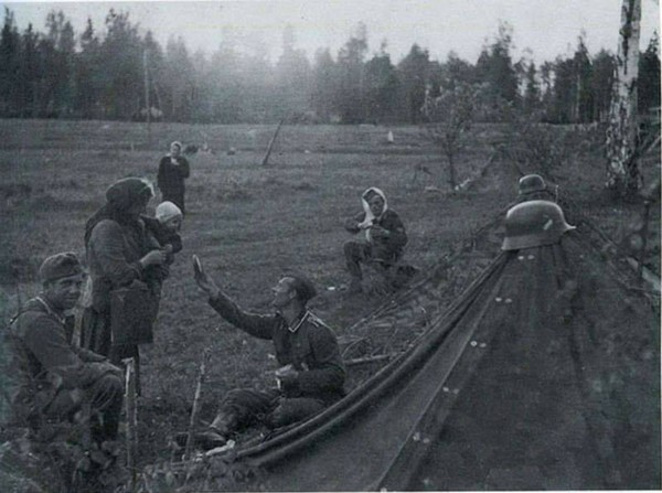 Một người lính Đức vui vẻ chia sẻ phần ăn ít ỏi của mình với hai mẹ con người Nga trong Chiến tranh Thế giới thứ 2 vào năm 1941.