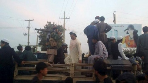 Chiến binh Taliban và người dân được nhìn thấy trên đầu trang của một chiếc xe quân sự ở Kunduz, một ngày sau khi Taliban nắm quyền kiểm soát thành phố ngày 29 tháng 9 năm 2015. REUTERS / STRINGER