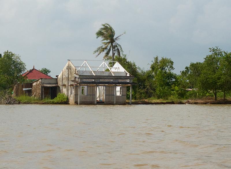 Một căn nhà sắp đổ xuống sông vì xói lở do nước dâng trên sông Gành Hào, Cà Mau. Ảnh: Hoàng Hường