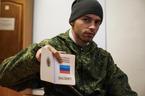 Người đàn ông trẻ ly khai do Nga hậu thuẫn trưng ra hộ chiếu của nước Cộng hoà nhân dân Luhansk tự xưng mà anh ta vừa nhận được. Ảnh chụp hôm Thứ Ba ngày 27 tháng 10 năm 2015. (AP Photo / Max Black)