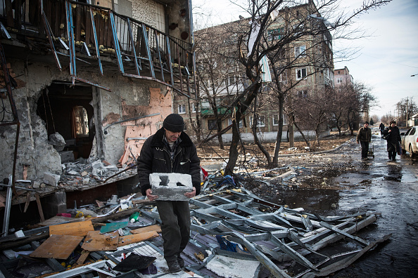 DEBALTSEVE, UKRAINE - FEBRUARY 25:  A man salvages cinder blocks from a destroyed building on February 25, 2015 in Debaltseve, Ukraina. After approximately one month of fighting, Russian backed rebels successfully forced Ukrainian troops to withdraw from the town on February 18. The town is considered an asset to both Ukrainians and the rebels due to the railway station and it's connection to other eastern Ukranian towns.  (Photo by Andrew Burton/Getty Images)