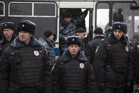 Police officers stand guard during an opposition rally in Pushkin Square in Moscow, Russia, Saturday, Dec. 12, 2015. Police report that over a dozen participants in an opposition rally held in support of the Russian constitution were detained. The Day of the Constitution is marked on Dec. 12 in Russia. (AP Photo/Pavel Golovkin)