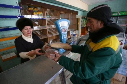Một người dân nhận đang nhận bánh mì miễn phí của quân đội Ukraina, tại một cửa hàng địa phương ở làng Pavlopil, Donetsk khu vực phía đông của Ukraina (AFP Photo / Aleksey Filippov)