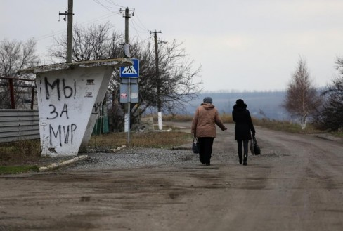 """Người dân đi bộ qua nhà chờ xe buýt trên tường viết """"Chúng tôi mong hòa bình"""", tại làng Pavlopol – Donetsk, miền đông Ukraina (AFP Photo / Aleksey Filippov)"""