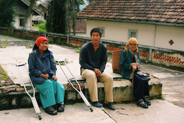 Trần Hùng John chụp ảnh cùng người dân trong chuyến đi xuyên Việt của mình.