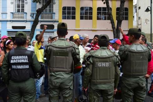 Những người biểu tình trước tòa nhà của cố Tổng thống Hugo Chavez tại Caracas nhưng được ngăn cách bằng hàng rào cảnh sát ngày 06-1-2016 (AFP Photo / Ronaldo Schemidt)
