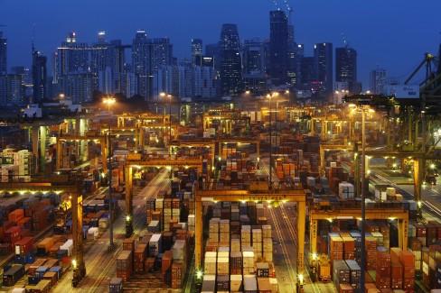 Đường chân trời của khu kinh doanh trung tâm Singapore được nhìn thấy vào lúc hoàng hôn và các hoạt động liên tục tại một cảng PSA International tại Singapore ngày 25 tháng 9 2013