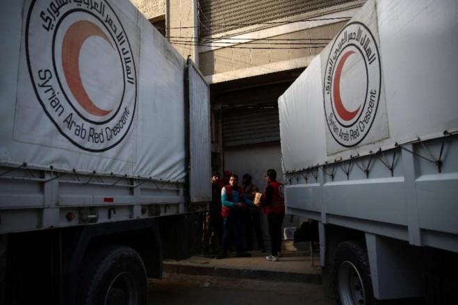 Các thành viên của Hội Trăng lưỡi liềm đỏ tại Syrian đang dỡ bưu kiện cứu trợ từ một chiếc xe tải 13-2-2016 tại thành phố Douma do phiến quân kiểm soát, phía đông bắc của thủ đô Damascus (AFP Photo / Abd Doumany)