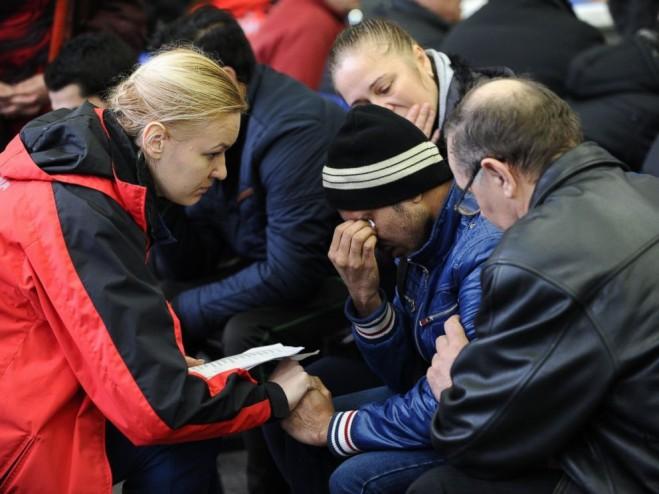 Nhân viên thuộc Bộ Tình trạng khẩn cấp Nga đang an ủi một người thân bị chết trong vụ tan nạn máy bay tại sân bay Rostov-on-Don, Nga, 19/3/2016.