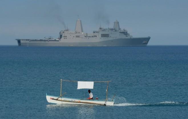 Một ngư dân Philippines được nhìn thấy gần chiến hạm vận tải đổ bộ của Hải quân Mỹ USS Green Bay (LPD-20) trong khi diễn tập đổ bộ trên một bãi biển ở San Antonio, tỉnh Zambales, tại vị trí cách Bãi cạn Scarborough trên Biển Đông khoảng 137 dặm (220km) về phía đông, vào ngày 21 tháng 4 năm 2015, như một phần trong cuộc tập trận chung hàng năm Philippine – Mỹ. (Ted Aljibe / AFP / Getty Images).