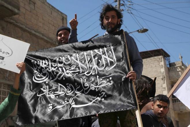 (Hosam Katan / Reuters) Người dân dương lá cờ của Mặt trận Nusra trong một cuộc biểu tình kỷ niệm ngày dành quyền kiểm soát Idlib khoảng một tháng trước đây và kêu gọi thực hiện các luật Hồi giáo Sharia, trong khu phố Al-Sakhour Aleppo 24/04/2015.