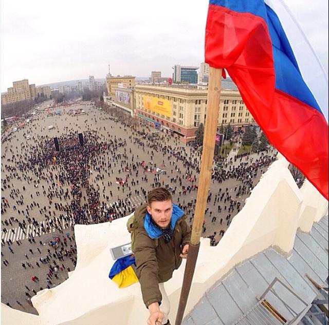 Một người đàn ông trẻ từ Saint Petersburg - Nga tên Michael Ronkainen hạ lá cờ Ukraina xuống và thay bằng lá cờ Nga trên tòa nhà Hội đồng thành phố Kharkov ngày 10 – 03 -2014